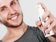 Homme appliquant le cosmétique de jet à ses cheveux image stock