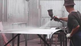 Homme appliquant le feuillard anti-corrosif de revêtement de poudre avec le pistolet de pulvérisation dans l'usine banque de vidéos