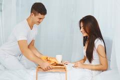 Homme apportant le petit déjeuner de femme dans le lit Images libres de droits