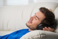 Homme appréciant la musique se trouvant sur le divan Image libre de droits