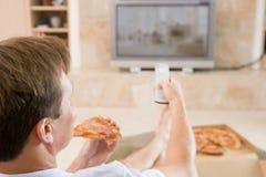 Homme appréciant la pizza tout en regardant la TV Images stock
