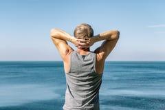 Homme appréciant la vue et l'air frais sur l'océan Voyage et un mode de vie sain photo libre de droits