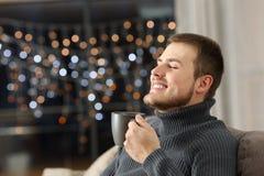 Homme appréciant le café à la maison pendant la nuit photographie stock