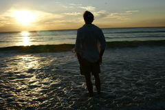 Homme appréciant le coucher du soleil Photos stock