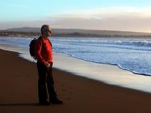 Homme appréciant le coucher du soleil par l'océan photographie stock libre de droits