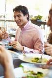 Homme appréciant le repas au restaurant extérieur avec des amis Images libres de droits