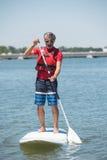 Homme appréciant le tour sur le lac avec le paddleboard Image libre de droits