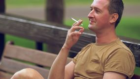 Homme appréciant un extérieur de fumée sur un banc banque de vidéos