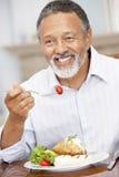 Homme appréciant un repas à la maison images stock