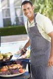 Homme appréciant un repas de Barbequed dans le jardin Image libre de droits