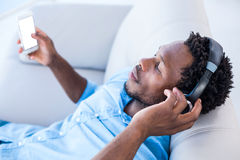 Homme appréciant la musique tout en détendant sur le sofa Images stock