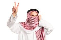 Homme arabe avec le visage couvert faisant des gestes la victoire Photos stock