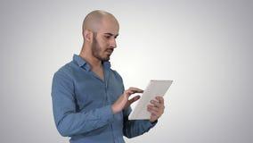 Homme arabe bel d'affaires utilisant le comprimé sur le fond de gradient clips vidéos