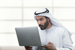 Homme Arabe d'affaires regardant étonné son ordinateur portable Image stock