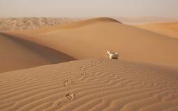 Homme arabe dans le kandoura se reposant au-dessus d'une dune et jouant avec le sable Photo stock