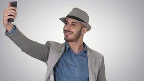 Homme Arabe dans les vêtements sport marchant et faisant le selfie sur le fond de gradient clips vidéos