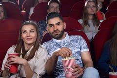 Homme Arabe et femme caucasienne mangeant du maïs éclaté au cinéma Photographie stock