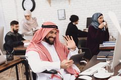 Homme arabe handicapé dans le fauteuil roulant fonctionnant dans le bureau L'homme parle sur le comprimé photographie stock