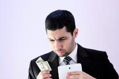Homme arabe triste d'affaires avec l'argent et le comprimé Images stock