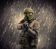 Homme armé de terroriste avec le masque sur le fond pluvieux photo stock