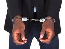 Homme arrêté avec les mains menottées Photo stock