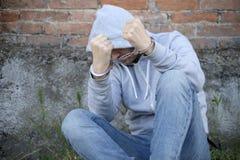 Homme arrêté dans des menottes sur le mur Image libre de droits