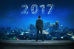 Homme arrière d'affaires de vue regardant 2017 sur le ciel Image libre de droits