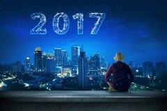 Homme arrière de vue regardant 2017 sur le ciel Photographie stock libre de droits