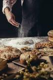 Homme arrosant de la farine sur la pâte Mains malaxant la pâte, vue cultivée photographie stock libre de droits