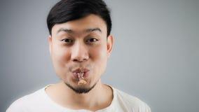 Homme asiatique avec l'os de poulet Images stock