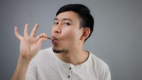 Homme asiatique avec l'os de poulet Photo stock