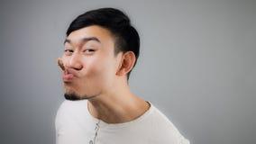 Homme asiatique avec l'os de poulet Image stock