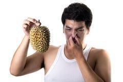 Homme asiatique avec la mauvaise odeur du durian à l'arrière-plan blanc Image stock