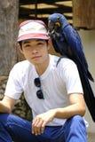 Homme asiatique avec le beau perroquet d'ara de jacinthe Images stock