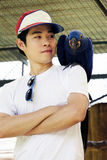 Homme asiatique avec le beau perroquet d'ara de jacinthe Photographie stock