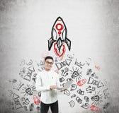 Homme asiatique avec le croquis d'ordinateur portable et de fusée Photos libres de droits