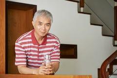Homme asiatique avec le verre de l'eau photographie stock libre de droits