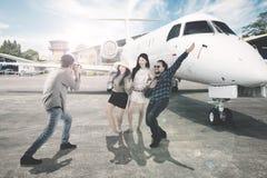 Homme asiatique avec ses amis près d'un avion Photos stock