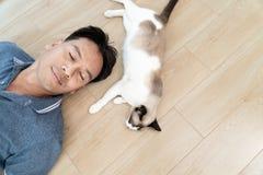 Homme asiatique avec un chat plus ancien se trouvant sur le plancher à la maison Photographie stock libre de droits