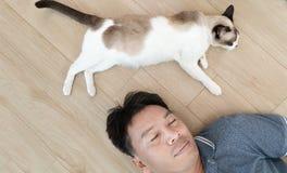 Homme asiatique avec un chat plus ancien se trouvant sur le plancher à la maison Photographie stock