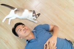 Homme asiatique avec un chat plus ancien se trouvant sur le plancher à la maison Images stock