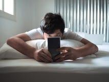 Homme asiatique décontracté avec le téléphone intelligent mobile se couchant sur le lit dans le matin photos stock