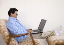 Homme asiatique détendant avec l'ordinateur portatif Images stock