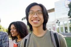 Homme asiatique d'étudiant gai se tenant dehors Photo stock
