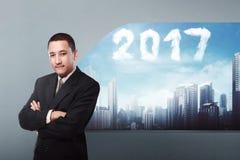 Homme asiatique d'affaires avec la forme de 2017 nuages sur le ciel Photographie stock libre de droits