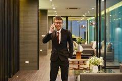 Homme asiatique d'affaires téléphonant dans le salon de luxe dans distant moderne photo stock