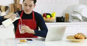 Homme asiatique dans le tablier rouge dans la cuisine