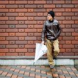 Homme asiatique dans une veste de Brown avec un parapluie clair Images stock