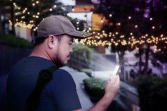 Homme asiatique de hippie à l'aide du téléphone intelligent à disposition avec le bokeh dans le parc à l'arrière-plan de temps de photos libres de droits
