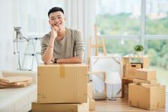 Homme asiatique de sourire aux boîtes emballées de carton photographie stock